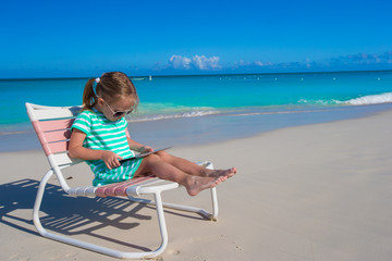 Little girl with laptop on beach during summer vacation