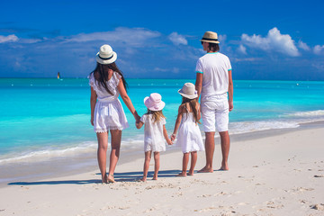 Back view of young family with two kids on caribbean vacation