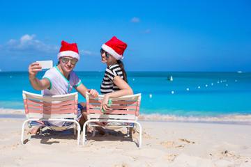Young couple in Santa hats enjoy beach vacation