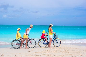 Young happy family riding bicycles duting beach vacation