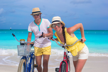 Young happy couple riding bikes during tropical vacation
