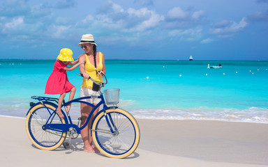 Happy mother and daughter riding bicycles on tropical beach