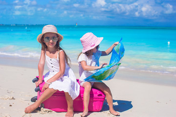 Adorable girls with big suitcase and map on tropical beach