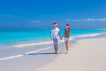 Young happy couple in red Santa hats on tropical beach