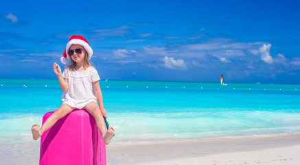 Little cute girl in Santa hat on suitcase at tropical beach