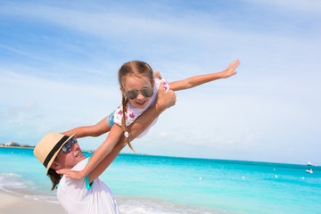 Happy dad have fun with his little cute girl during beach