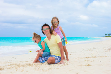 Adorable little girls and happy dad on tropical white beach