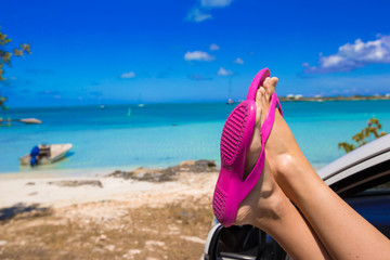 Pink flip Flops from the window of car on tropical beach