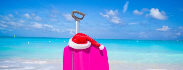 Closeup of pink suitcase and Santa Claus hat on beach
