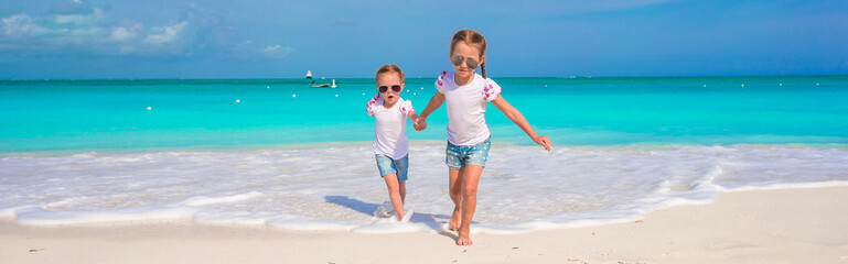 Little cute girls enjoy their summer vacation on the beach