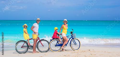 Zdjęcia na płótnie, fototapety, obrazy : Young family riding bicycles on tropical beach