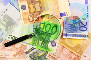 Magnifying glass over Euro paper notes. Financial needs