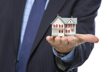 Male Real Estate Agent Holding Miniature House in Palm