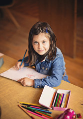 Beautiful smiling little girl drawing