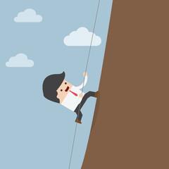 Businessman climbing on the rocks