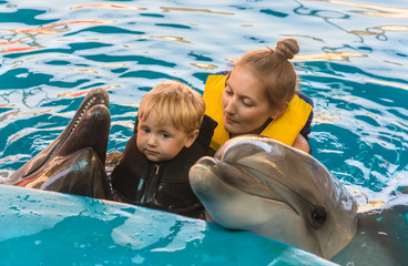 boy and mum float with dolphins in pool