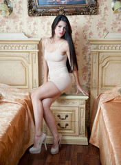 Young beautiful sexy woman in white short tight dress posing
