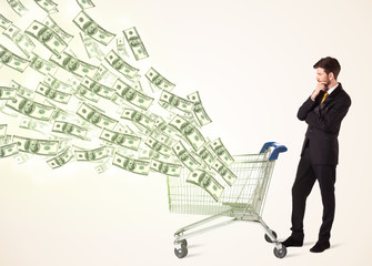 Businessman with shopping cart with dollar bills