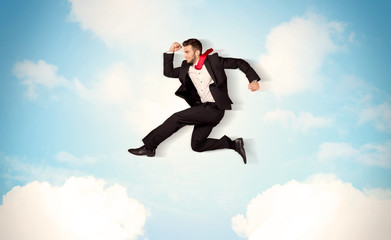 Business person jumping over clouds in the sky