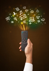 Hand with remote control and social media icons