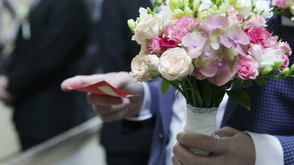 Groom with wedding bouquet and card