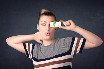 Young girl holding paper with green dollar sign