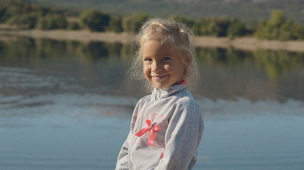 Little girl with incredibly expressive eyes standing near a pond