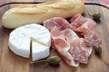 Appetizers board with Camembert, cured ham, salami and capers.