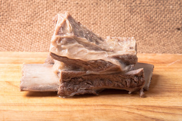 boiled meat with a bone on a wooden board