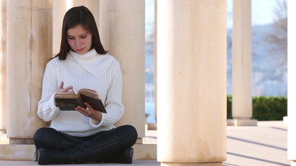 Young woman reading old book outside