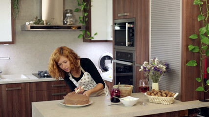 Woman putting chocolate cream on the cake