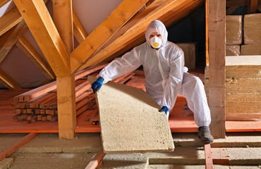 Man with rockwool panel installing insulation layer