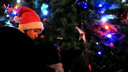 Beautiful woman in a fur coat and santa hat near christmas tree
