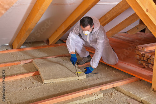 Man laying thermal insulation layer - cutting the panels - 74623973
