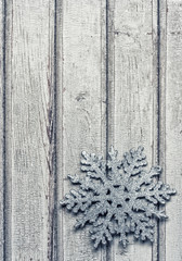 silver snowflake on the old wooden background