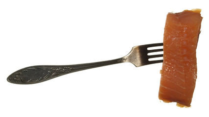 A piece of red fish on old metal fork isolated on a white backgr