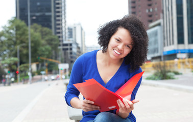 Lachende Studentin aus Südamerika mit Mappe in der Stadt