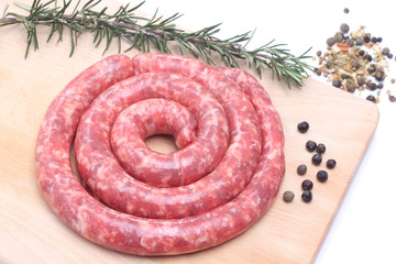 Raw sausage on wooden cutting board