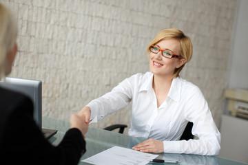 Blonde businesswoman in glasses handshake