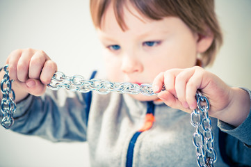 boy stretching metallic chain in hands