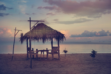 cafe table in the form of huts on the beach at sunset