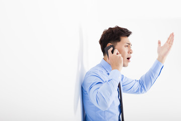 angry businessman talking on the phone in office