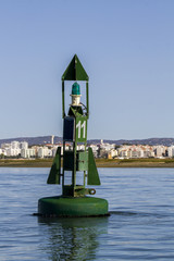 View of a floating green navigation buoy on the sea.