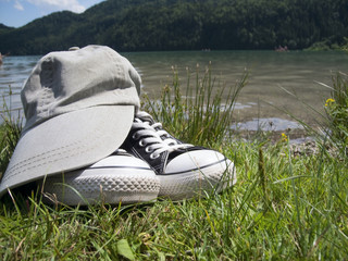 shoes and cap by the lake