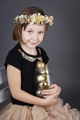 Little girl holding christmas balls in the jar