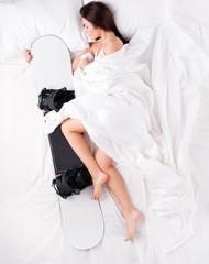 Beautiful woman sleeping and hugging snowboard