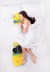 Young woman sleeping and hugging snowboard