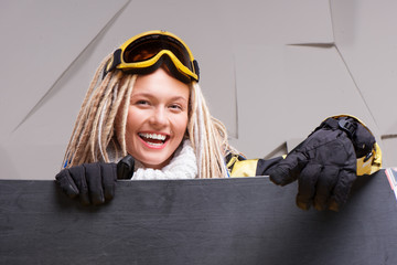 Smiling woman with dreadlocks looking out the snowboard