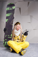 Smiling woman sitting on floor with snowboard