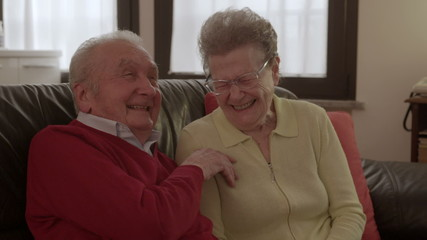 Elder couple cuddling and laughing on the couch